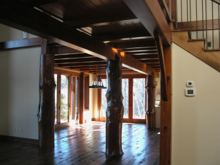 Round log post accents in Timber Frame Hybrid Home